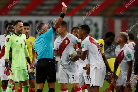 Referee Wilton Sampaio of Brazil shows the red card to Peru's Miguel Trauco, right, for fouling Colombia's Juan Cuadrado during a qualifying soccer match for the FIFA World Cup Qatar 2022 at the National stadium in Lima, Peru