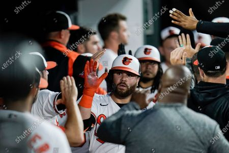 Baltimore Orioles' DJ Stewart is greeted in the dugout after hitting a two-run home run against Minnesota Twins starting pitcher Randy Dobnak during the fifth inning of a baseball game, in Baltimore. Orioles' Freddy Galvis scored on the home run