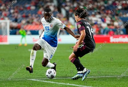 Costa Rica's Joel Campbell (12) works with the ball next to Mexico's Diego Lainez (14) during the first half of a CONCACAF Nations League soccer semifinal, in Denver