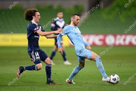 Florin Berenguer of Melbourne City passes the ball as Jay Barnett of the Victory challenges; AAMI Park, Melbourne, Victoria, Australia; A League Football, Melbourne Victory versus Melbourne City.