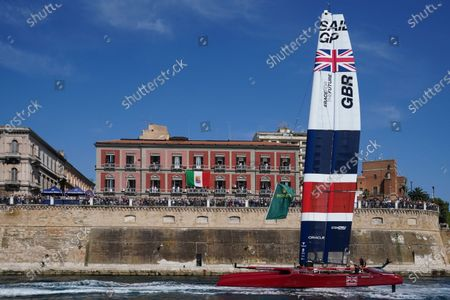 Great Britain SailGP Team helmed by interim skipper Paul Goodison are towed at pace on their foils past the crowd on the shore line during a practice session ahead of Italy SailGP, Event 2, Season 2 in Taranto, Italy. 04 June 2021. Photo: Bob Martin for SailGP.
