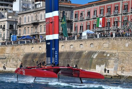 Stock Photo of Great Britain SailGP Team helmed by Paul Goodison are towed at pace on their foils past the crowd following a practice session ahead of Italy SailGP, Event 2, Season 2 in Taranto, Italy. 04 June 2021. Photo: Ricardo Pinto for SailGP.