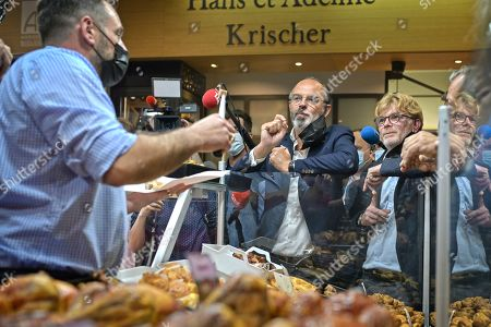 Former French Prime Minister Edouard Philippe (C) flanked by French Junior Minister of Parliament Marc Fesneau (R) talks with commercant