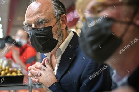 Former French Prime Minister Edouard Philippe (L) flanked by French Junior Minister of Parliament Marc Fesneau talks with commercant