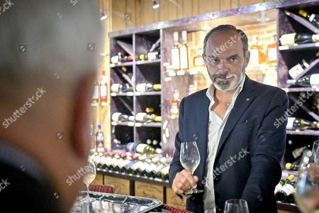 Stock Photo of Former French Prime Minister Edouard Philippe (R) drinks a glass of wine as he supports the French Junior Minister of Parliament Marc Fesneau (not visible) at the regional election