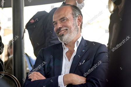 Former French Prime Minister Edouard Philippe smiles at a cafe as he supports the French Junior Minister of Parliament Marc Fesneau (not visible) at the regional election