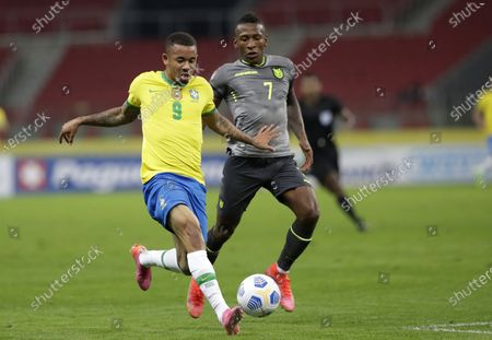 Brazil's Gabriel Jesus, left, and Ecuador's Pervis Estupinan fight for the ball during a qualifying soccer match for the FIFA World Cup Qatar 2022 at Beira-Rio stadium in Porto Alegre, Brazil