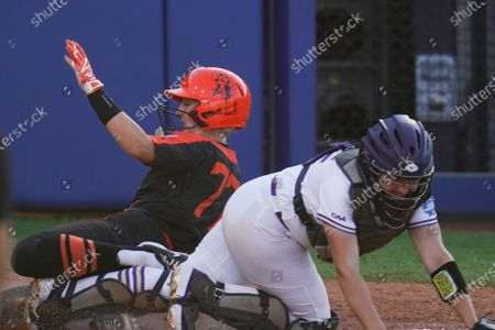 Oklahoma State's Reagan Wright, left, scores behind James Madison catcher Lauren Bernett, right, on a ball hit by Chelsea Alexander in the fifth inning of an NCAA Women's College World Series softball game, in Oklahoma City