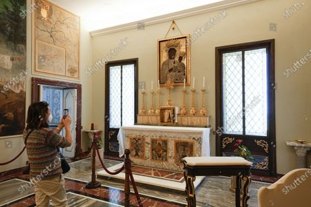 Visitor takes photos of the popes' private chapel, where Pope Francis went to pray with Pope Benedict XVI just after being elected in 2013, inside the Papal Palace in Castel Gandolfo, some 30 kilometers southeast of Rome, . As Covid-19 restrictions are slowly being lifted in Italy, thousands of people are returning to visit the extensive gardens and apartments at the Papal Palace of Castel Gandolfo in the Alban Hills near Rome, that for hundreds of years have been the summer retreat for Popes seeking to escape the suffocating heat of Rome