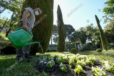 Worker waters flowers in the section of the gardens of the Papal Palace where Pope John Paul II used to gather in prayer, next to a statue of the Madonna, in Castel Gandolfo, some 30 kilometers southeast of Rome, . As Covid-19 restrictions are slowly being lifted in Italy, thousands of people are returning to see the extensive gardens and apartments at the Papal Palace of Castel Gandolfo in the Alban Hills near Rome, that for hundreds of years have been the summer retreat for Popes seeking to escape the suffocating heat of Rome