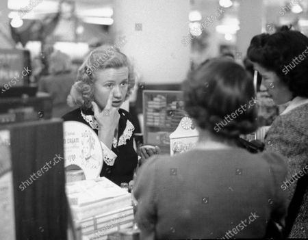 Priscilla Lane demonstrating to her customers, the proper way to apply face makeup.