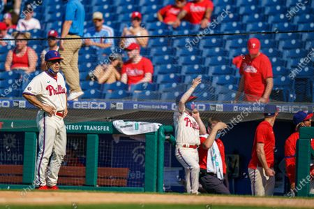Philadelphia Phillies manager Joe Girardi, left, looks on as the safety netting snapped during the eighth inning of a baseball game against the Washington Nationals, in Philadelphia