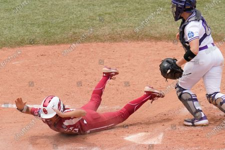 Oklahoma's Rylie Boone, left, celebrates after scoring behind James Madison catcher Lauren Bernett, right, on a hit by an Tiara Jennings in the seventh inning of an NCAA Women's College World Series softball game, in Oklahoma City