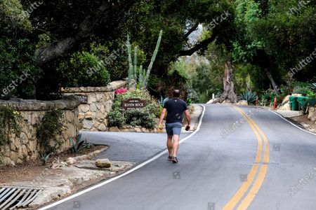 """Stock Picture of Man walks past a community gate of the home of Prince Harry The Duke of Sussex and Meghan Markle The Duchess of Sussex, in Montecito, Calif. A spokesperson said that the couple welcomed their child Lilibet """"Lili"""" Diana Mountbatten-Windsor at 11:40 a.m. Friday at the Santa Barbara Cottage Hospital"""