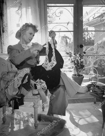 Actress Billie Burke selecting clothes to give to UNRRA.