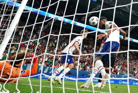 Stock Photo of United States' Jordan Siebatcheu Pefok (16) tries to head the ball into the net against Mexico's Guillermo Ochoa (13) during the CONCACAF Nations League championship soccer match, in Denver