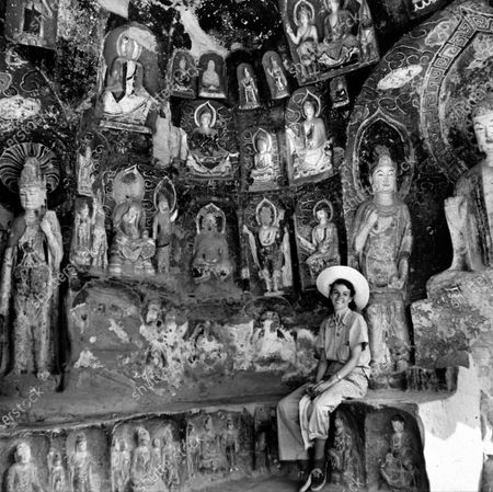 Shelley Mydans (nee Smith), wife of LIFE photographer Carl Mydans, posing amid carved Buddha statues inside a cave during their tour of China.