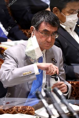Japanese Administrative Reform Minister Taro Kono drinks water as he listens to a question at Upper House's audit committee session at the National Diet in Tokyo on Monday, June 7, 2021.