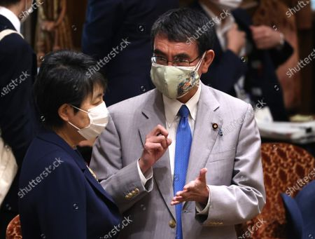 Japanese Administrative Reform Minister Taro Kono (R) chats with Juctice Minister Yoko Kamikawa (L) before starting Upper House's audit committee session at the National Diet in Tokyo on Monday, June 7, 2021.