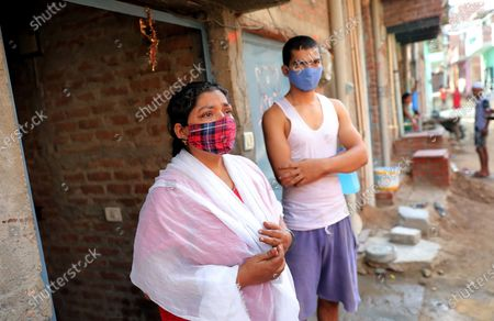 Roma sharma, widow of Sri Kant Sharma who died during the second wave of Covid19 on 08 May 2021 and her son Mishon Sharma stand outside their house in Yusufpur Chak Saberi village in Dadri, Uttar Pradesh, India, 06 June 2021 (issued 07 June 2021). Sri Kant Sharma died due to the lack of proper treatment and unavailability of beds at hospitals during the peak of the second wave. Sri Kant Sharma was the only earning member of the family and now widow Roma lives with three children who are studying but unsure to continue their study due to the death of their father as he was the sole earning member in the family. Thousands of families and children lost their only earning parent and earning member of the family to COVID-19 and struggling to continue with their life with collective loss and trauma the pandemic has left. According to the National Commission for Protection of Child Rights 4,860 boys and 4,486 girls have been affected due to loss of either single or both parents. The number could be higher as many states were unable to provide their data to the commission for various reasons.