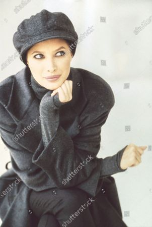 Model Christy Turlington, in a studio, wearing a short trenchcoat in gray cashmere and wool by Escada over a gray silk and cotton turtleneck by Calvin Klein, with a gray hat by Eric Javits. Hair by Roque for Oribe. Makeup by Mary Greenwell.