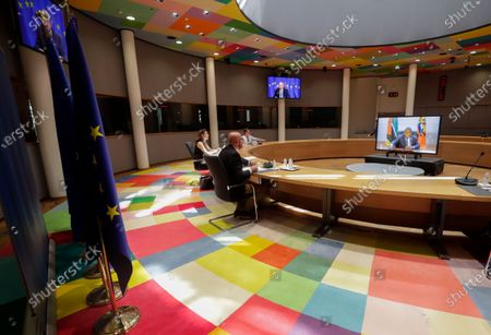 European Council President Charles Michel (2-L) during a video meeting with Mozambique's President Filipe Nyusi (R on screen) at the European Council building in Brussels, Belgium, 07 June 2021.