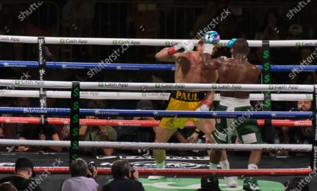 Floyd Mayweather Jr, 44 throws a left to the head of Logan Paul, 26 in an exhibition fight at the Hard Rock Stadium