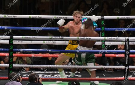 Floyd Mayweather Jr, 44 covers up as Logan Paul, 26 lifts his hands in an exhibition fight at the Hard Rock Stadium