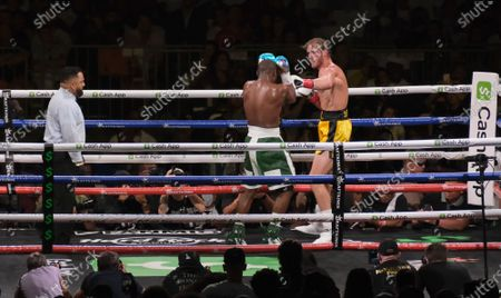 Floyd Mayweather Jr, 44 covers up as Logan Paul, 26 moves in with a left in an exhibition fight at the Hard Rock Stadium