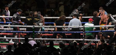 Logan Paul, 26 is checked by his team at the end of an exhibition fight with Floyd Mayweather Jr, 44, at the Hard Rock Stadium