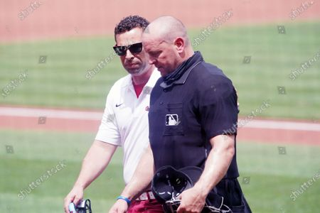 A St. Louis Cardinals trainer helps home plate umpire Scott Barry from the field after Berry took a foul tip to the top of his head head during the fourth inning during the Cincinnati Reds-St. Louis Cardinals baseball game at Busch Stadium in St. Louis