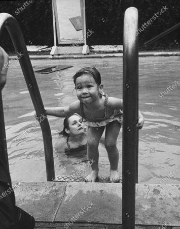 Stock Picture of 2 year old, Mary Frances Crosby, daughter of Bing Crosby, as she won her Red Cross Merit Badge for beginner swimmers.