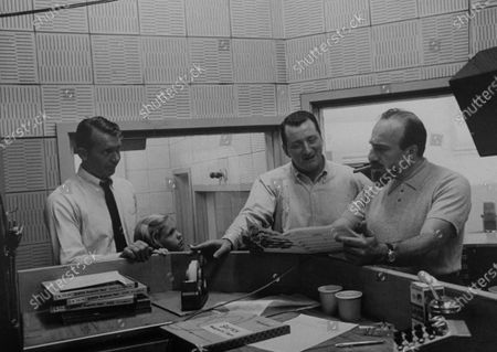 Musician Mitch Miller (R) looking over music for children's records.