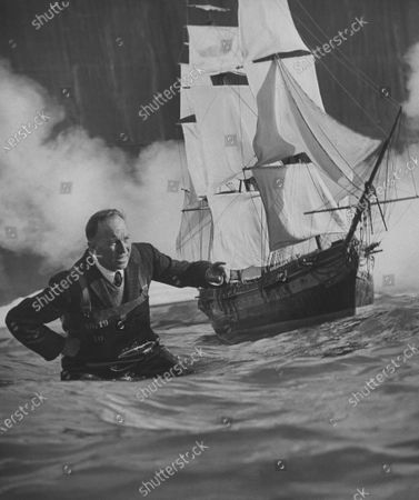 Movie special effects dir. John Fulton wading in tank w. large model of sailing ship as he sets up scene on set in movie studio.