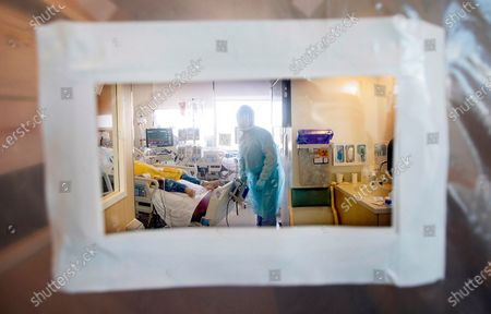 A view of pulmonologist Dr. Jason Prasso through a plastic door after he was checking on patient Gilbert Torres, age 30, inside Martin Luther King, Jr. Community Hospital on JANUARY 20, 2021 in Los Angeles, CA. (Francine Orr / Los Angeles Times)
