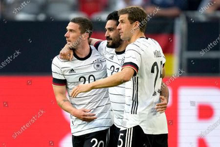 Germany's scorer Ilkay Gundogan, center, and his teammates Robin Gosens, left, and Thomas Mueller, right, celebrate their side's second goal during the international friendly soccer match between Germany and Latvia in Duesseldorf, Germany