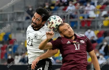 Germany's Ilkay Gundogan, left, and Latvia's Arturs Zjuzins challenge for the all during the international friendly soccer match between Germany and Latvia in Duesseldorf, Germany