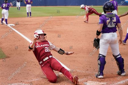 Stock Photo of Oklahoma's Lynnsie Elam (22) scores behind James Madison catcher Lauren Bernett, right, in the fourth inning of an NCAA Women's College World Series softball game, in Oklahoma City