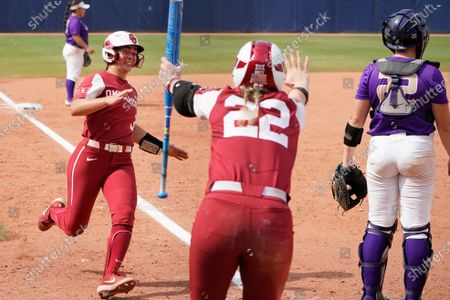 Stock Picture of Oklahoma's Grace Lyons (3) runs home behind James Madison catcher Lauren Bernett, right, as teammate Lynnsie Elam (22) signals in the fifth inning of an NCAA Women's College World Series softball game, in Oklahoma City