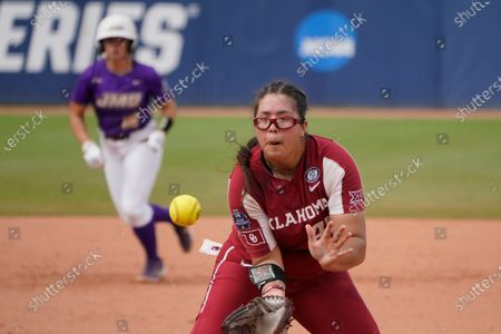 Stock Image of Oklahoma pitcher Giselle Juarez fields a ball hit by James Madison's Lauren Bernett and throws to first base for the final out in an NCAA Women's College World Series softball game, in Oklahoma City