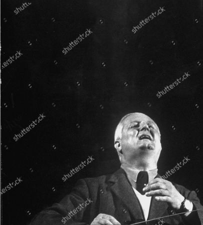 During an opera at the Glyndebourne Festival, Fritz Busch is opening his mouth like a singer delivering an impassioned aria.