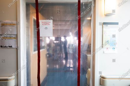 A view of pulmonologist Dr. Jason Prasso seen through a plastic door checking on Gilbert Torres, age 30, inside Martin Luther King, Jr. Community Hospital on JANUARY 20, 2021 in Los Angeles, CA.