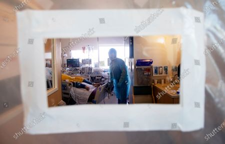A view of pulmonologist Dr. Jason Prasso through a plastic door after he was checking on patient Gilbert Torres, age 30, inside Martin Luther King, Jr. Community Hospital on JANUARY 20, 2021 in Los Angeles, CA.
