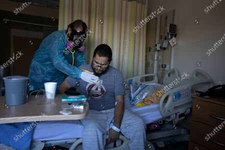 Stock Photo of Dr. Jack Geoula, left, examines Gilbert Torres, age 30, right as he is sitting up on his bed at Martin Luther King, Jr. Community Hospital (MLKCH) on Feb. 6, 2021 in the Willowbrook neighborhood of southern Los Angeles County, CA. Gilbert Torres is a covid positive and he was placed on a ventilator. He is better and is going home today.