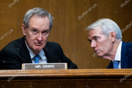 Sen. Mike Crapo, R-Idaho, speaks with Sen. Rob Portman, R-Ohio, during a Senate Finance Committee hearing on the IRS budget request on Capitol Hill in Washington