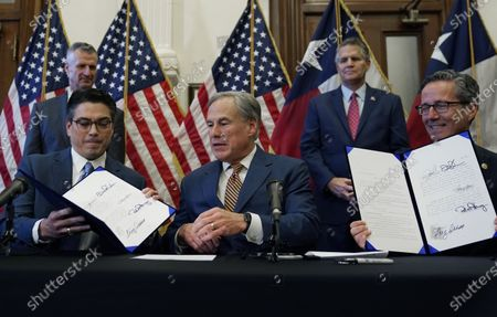 Stock Image of With the help of state Rep. Chris Paddie, left, and state Sen. Kelly Hancock, right, Texas Gov. Greg Abbott, center, displays two energy related bills he signed, in Austin, Texas. Abbot signed legislation into law to reform the Electric Reliability Council of Texas (ERCOT) and weatherize and improve the reliability of the state's power grid