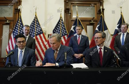 With state Rep. Chris Paddie, left, and state Sen. Kelly Hancock, right, looking, Texas Gov. Greg Abbott, center, signs two energy related bills, in Austin, Texas. Abbot signed legislation into law to reform the Electric Reliability Council of Texas (ERCOT) and weatherize and improve the reliability of the state's power grid