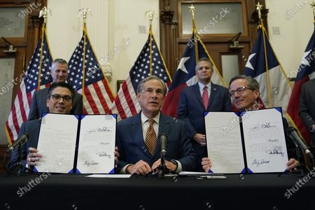 Stock Photo of With the help of state Rep. Chris Paddie, left, and state Sen. Kelly Hancock, right, Texas Gov. Greg Abbott, center, speaks as two energy related bills he signed are displayed, in Austin, Texas. Abbot signed legislation into law to reform the Electric Reliability Council of Texas (ERCOT) and weatherize and improve the reliability of the state's power grid