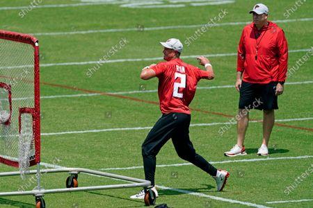 Atlanta Falcons quarterback Matt Ryan throws a baseball into a net as head coach Arthur Smith looks on during the team's mini camp football practice, in Flowery Branch, Ga