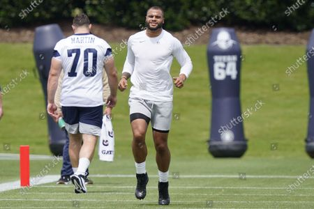 Dallas Cowboys quarterback Dak Prescott, right, warms-up as teammate offensive guard Zack Martin, left, walks by during an NFL football team practice, in Frisco, Texas